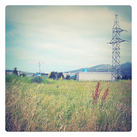 hierba seca, sol, tendido electrico, cielo con nubes, campo verde y amarillo, paisaje a las afueras, verano en Torrelavega