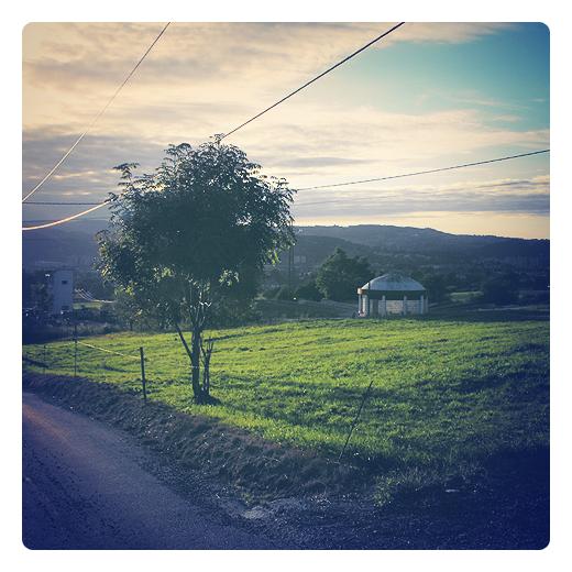 luz de septiembre, dias acortados, ultima luz, atardecer, ocaso, luz crepuscular, horizonte de nubes y montañas, cables electricos, paisaje con arbol, deposito de agua de consumo humano en Torrelavega
