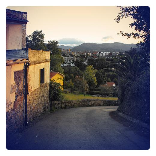 curva cerrada, cambio de dirección, pendiente de terreno, bajada, paisaje de casas y montañas, reflejos sol, atardecer, Las Traidas, fotografia de Torrelavega