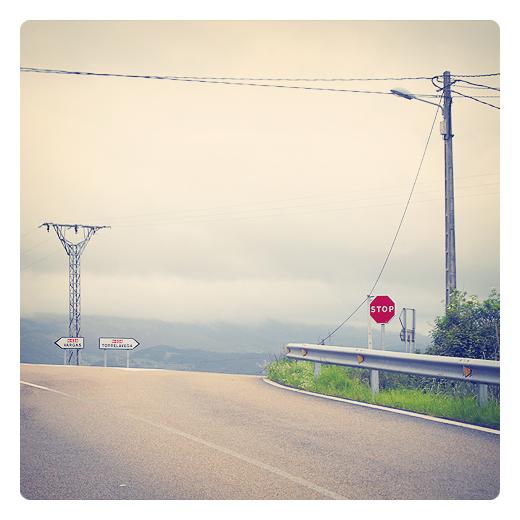 encrucijada, cruce de caminos, bifurcación, señalizacion vertical, red electrica, carretera comarcal, dia nublado, horizonte de montañas con niebla, fotografia de Torrelavega