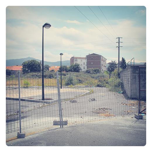 redil, cercado para el ganado, cerramiento, excrementos, espacio urbano abandonado, aceras, farolas, horizonte de montañas, fotografia de Torrelavega
