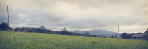 caida suave, pendiente, desnivel de terreno, red electrica, postes de la luz, horizonte de montañas, nubes, Caserios, fotografia de Torrelavega