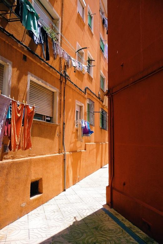 casas humildes, color naranja, barrio, ropa tendida, sombras, dia soleado. Barrio de La Inmobiliaria en Torrelavega