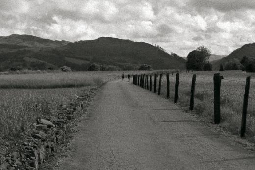 Pareja caminando por una carretera solitaria, Las Excavadas en Torrelavega, horizonte de montañas