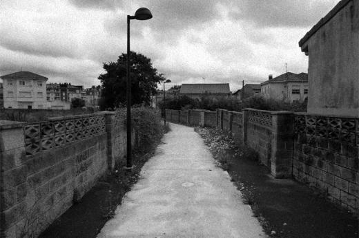senda, camino entre casas, farola, abandono