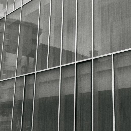 edificios reflejados en un muro cortina de cristal, detalle arquitectura