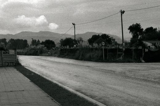 Carretera solitaria con las cunetas pobladas de plumeros, postes de luz y señales. Horizonte de montañas, día lluvioso