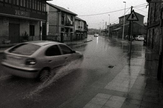 Un coche salpica agua al pasar por un charco en una carretera entre casas, Campuzano