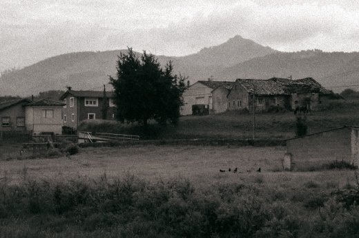 Un grupo de casas sobre una pequeña loma, al fondo el monte Dobra. Niebla, gallinas en un prado.