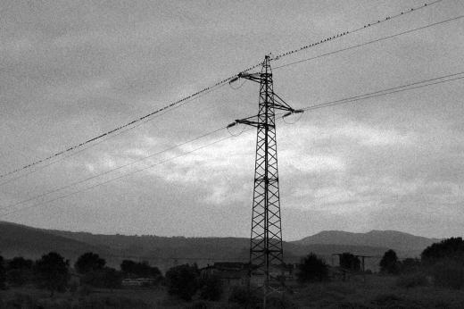 Un grupo de pájaros en un cable de alta tensión, horizonte de montañas, día nublado